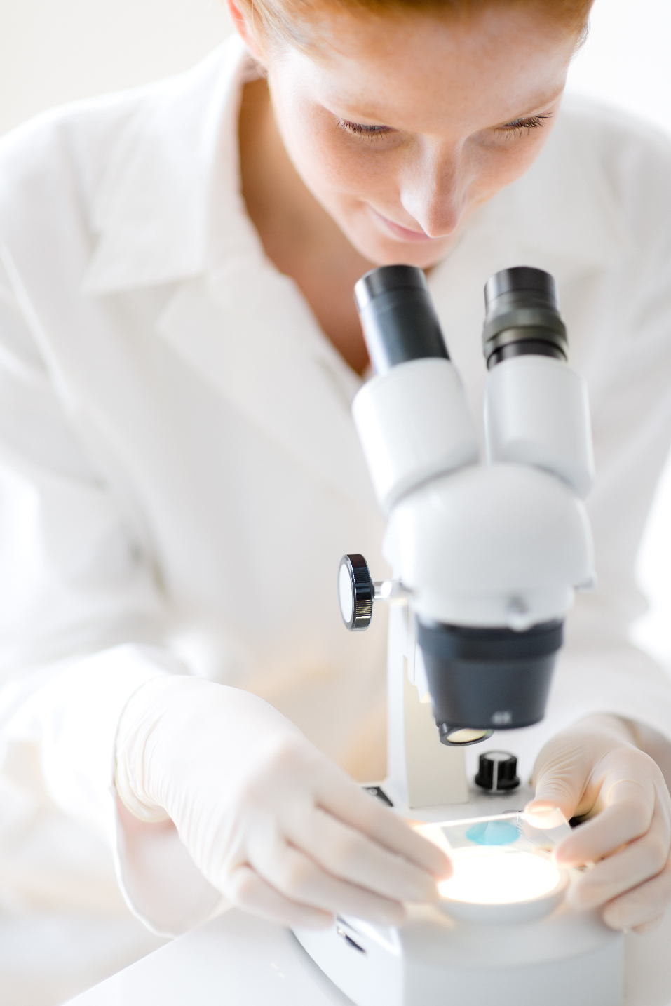 woman looking at sample under microscope